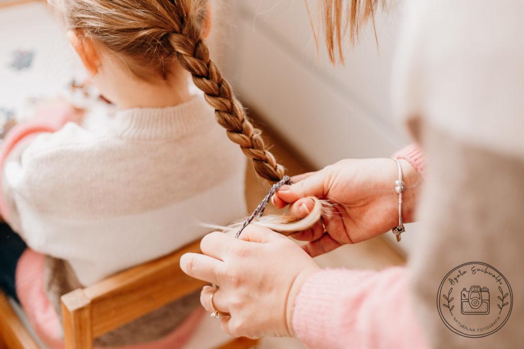 mama zaplata włosy córce na domowej sesji zdjęciowej